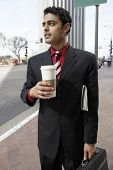 Young mixed race businessman with takeout coffee cup standing on city street