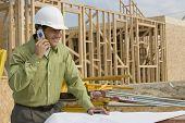 Lächelnd Bauarbeiter mit Handy und Blaupausen am Standort