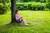 Pretty Teenager Girl In Casual Clothes With Digital Tablet On Her Knees Sitting In The Park