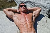 Attractive Young Muscle Man Sunbathing On Rock