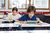 Little school boy using digital tablet with girl studying in background at classroom