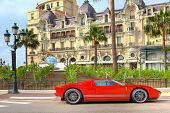 MONTE CARLO, MONACO - JULY 13: Red sports car and Hotel de Paris - luxury hotel opened in 1863, contains rooms and suites with exclusive city and sea views in Monte Carlo, Monaco on July 13, 2013.