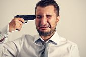 image of weeping  - businessman with gun wants to commit suicide - JPG