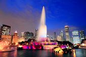 Chicago skyline with skyscrapers and Buckingham fountain in Grant Park at dusk lit by colorful light