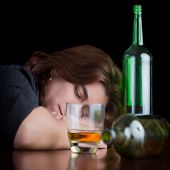 Dark dramatic image of a drunk and tired woman with a glass and a bottle of whisky on the table