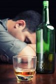 Blue toned image of a drunk and depressed man isolated on black