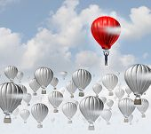 foto of competition  - The best leadership concept with a group of grey hot air balloons in the sky and a red aircraft guided by a business leader rising above the competition as a success metaphor for leadership - JPG