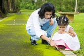 Indian family outdoor activity. Candid portrait of mother and daughter exploring on nature, outdoors
