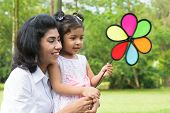 Happy Indian family outdoor activity. Candid portrait of parent and child playing windmill at garden park.