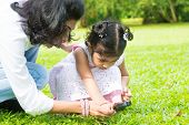 Cute Indian girl peeking through magnifying glass with parent on green lawn. Mother and daughter exp