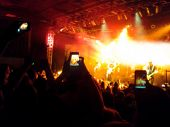 a crowd of people at a concert (focus on the phone photo)