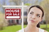 Thoughtful Pretty Mixed Race Woman In Front of Home and House For Sale Real Estate Sign Looking Up and to the Side.