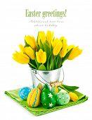 easter eggs with yellow tulips in bucket isolated on white background