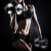 stock photo of sportswear  - Brutal athletic woman pumping up muscules with dumbbells - JPG