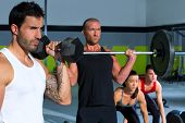 gym group with weight lifting bar and dumbbells workout in crossfit exercise