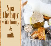 Honey and milk spa with oils and honey on wooden table close-up