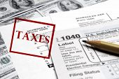 picture of irs  - Current tax forms and pencil on money with stamp for taxes - JPG