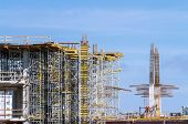 stock photo of scaffolding  - Incomplete building under construction with scaffolding and reinforced steel - JPG