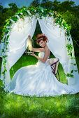 Beautiful bride with chaming red hair sitting under the wedding arch. Wedding dress and accessories.
