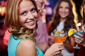 Portrait of cheerful girl holding cocktail in martini glass and looking at camera on background of h