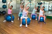 Fitness class holding dumbbells on exercise balls in studio at the gym