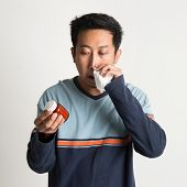 Asian male sneezing and holding medicine bottle, on plain background