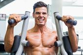 Determined young muscular man working on fitness machine at the gym