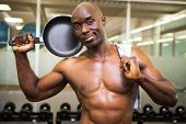 Portrait of a smiling shirtless muscular man holding frying pan in gym