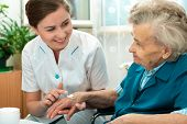 stock photo of nurse  - Nurse assists an elderly woman with skin care and hygiene measures at home - JPG