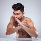 naked man sitting and posing in a karate defence position, fooling around