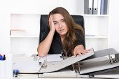 Young Frustrated Woman Is Sitting In Front Of A Pile Of Files