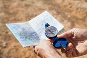 Hiker holding his compass and map in the countryside on a sunny day