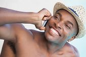 Smiling man talking on phone by the pool on a sunny day
