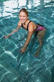 Fit happy blonde using underwater exercise bike in swimming pool at the leisure centre