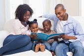 stock photo of cuddle  - Happy family on the couch reading storybook at home in the living room - JPG