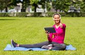 fitness, park, technology and sport concept - smiling african american woman with tablet pc and head