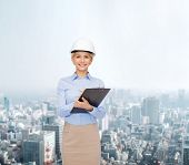 building, developing, construction and architecture concept - smiling businesswoman in white helmet