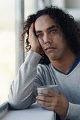 Bored guy with curly hair holding a hot beverage looking out the window