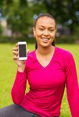 fitness, park, technology and sport concept - smiling african american woman showing smartphone outd