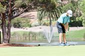 Male teen golfer preparing to putt
