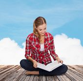 education and leisure concept - smiling young woman sitting on floor with book