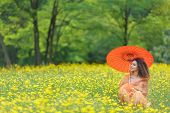 Beautiful stylish young woman with curly hair holding a colorful orange parasol in a meadow filled w