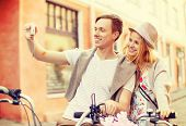 summer holidays, travel, vacation, tourism and dating concept - travelling couple with bicycles taki