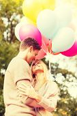 summer holidays, celebration and dating concept - smiling couple with colorful balloons in the park