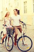 summer holidays, bikes, love, relationship and dating concept - smiling couple with bicycles in the