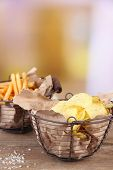 Tasty potato chips and french fries in metal baskets on wooden table, on light background