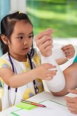 Little Asian Girl Bandaging Dad's Arm