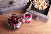 Dried hibiscus tea in glass jar, brown sugar  in box on wooden background