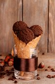 Tasty chocolate ice cream in waffle cone on brown wooden background