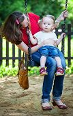 Happy mother and daughter sitting on swing